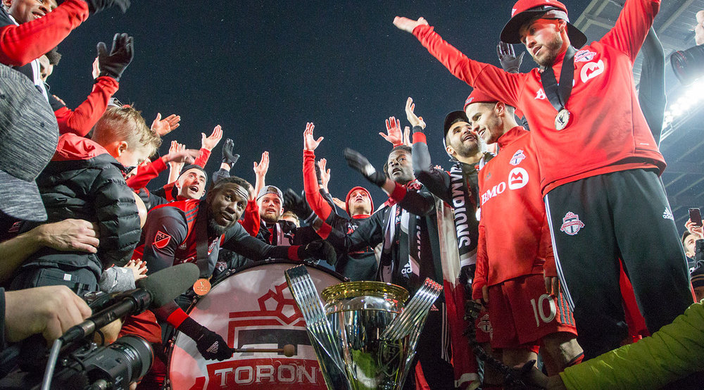 Toronto FC celebrates the treble with the south end supporter's section with a thunder clap. Image by Dennis Marciniak of denMAR Media.