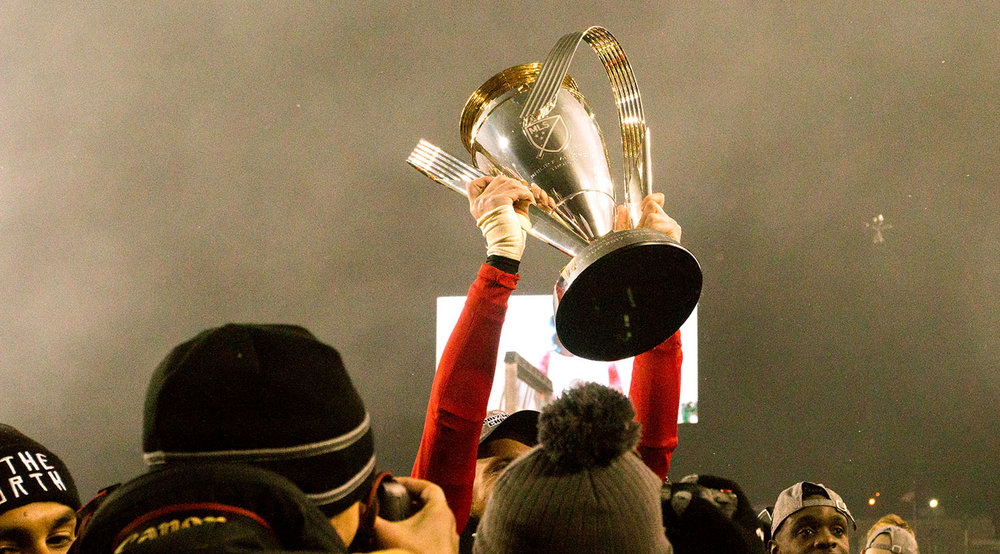 The trophy is lifted in the south end to celebrate the win for Toronto FC's 2017 MLS Cup win. Image by Dennis Marciniak of denMAR Media.