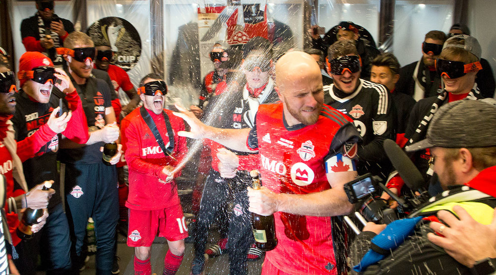 Sebastian Giovinco spraying Michael Bradley with champagne in the locker room after taking home the 2017 Major League Soccer Cup. Image by Dennis Marciniak of denMAR Media.