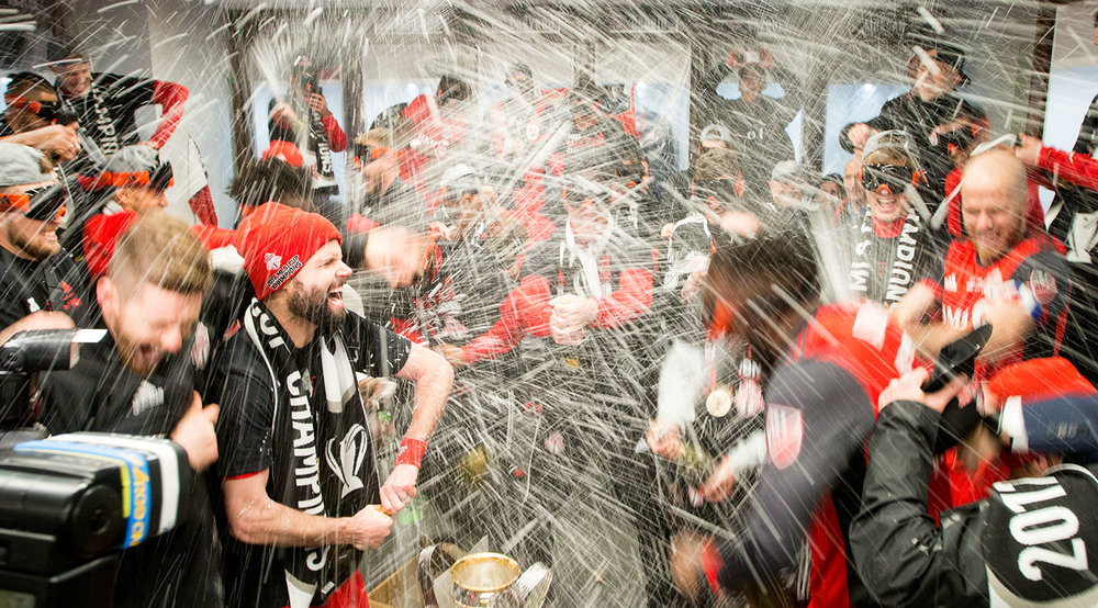 Drew Moor celebrates in the locker room as beer and champagne get sprayed everywhere during the MLS Cup 2017 at BMO Field. Image by Dennis Marciniak of denMAR Media.