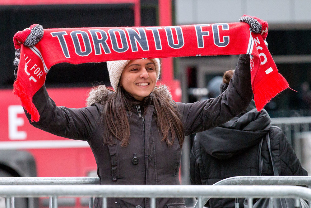 A Toronto FC Supporter raises their scarf high up in the ahead of the 2017 MLS Cup Parade. Image by Dennis Marciniak of Denmar Media.