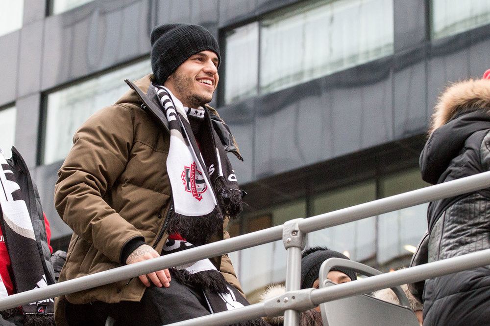 Sebastian Gioivnco attop the parade bus during the Toronto FC players celebrate with the trophy during the Toronto FC 2017 MLS Cup Parade. Image by Dennis Marciniak of Denmar Media.