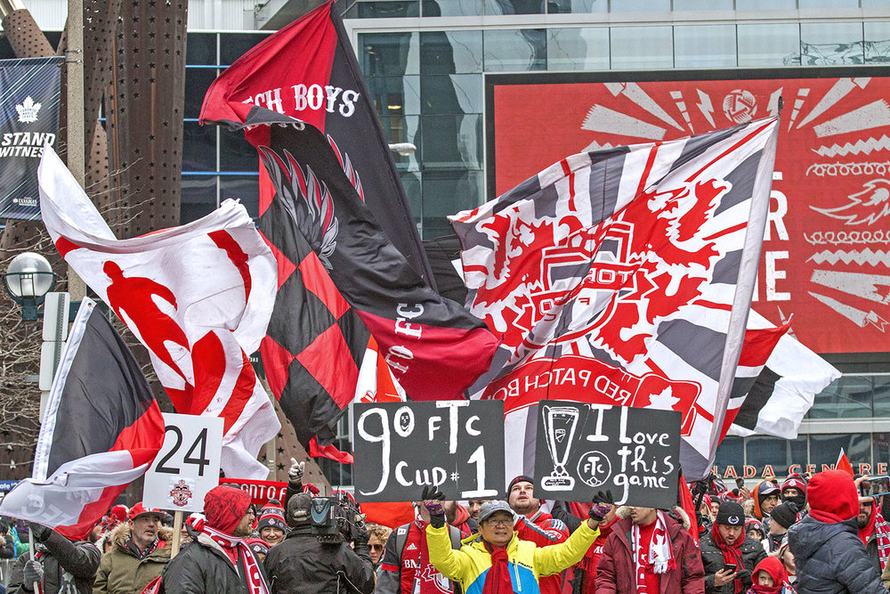 Toronto FC Supporter's march down the street during the Toronto FC 2017 MLS Cup Parade. Image by Dennis Marciniak of Denmar Media.