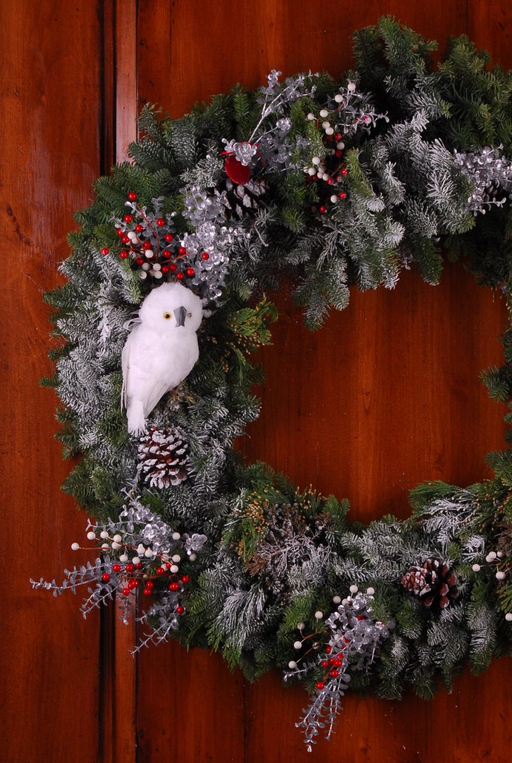 Snowy white owls perched on a fresh green wreath