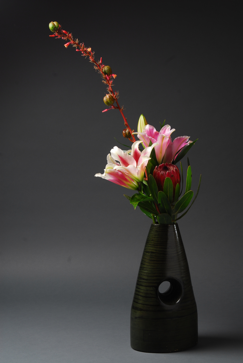 Green stripped vase with hole it the center filled with tall stem of Yucca, star gazer lilies and pink mink protea