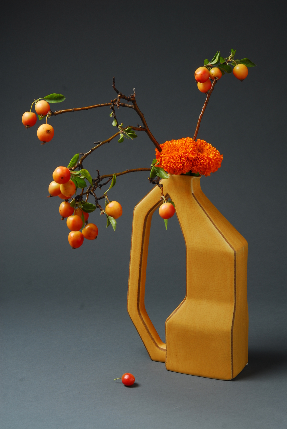 Tall yellow vase with crab apples and orange marigold