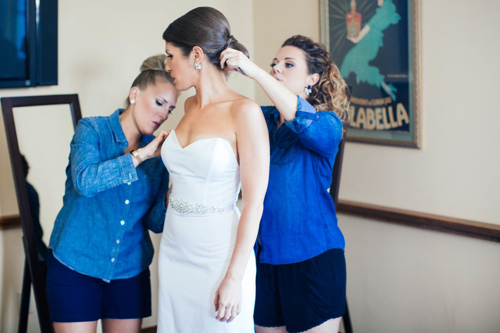 Photo of Bridesmaids helping bride get ready shot by a Minneapolis Wedding Photographer