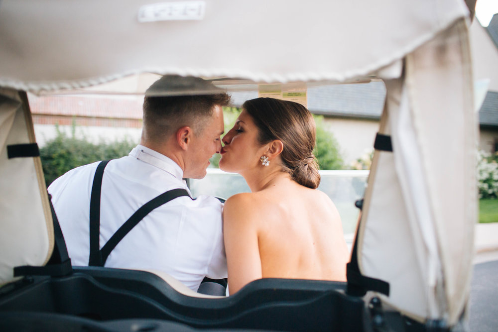 Bride and Groom Kissing in a Golf Cart
