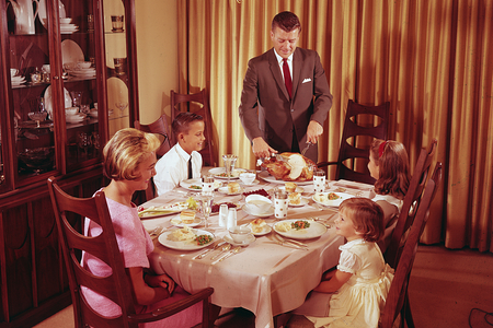 Man Carving Turkey For Family Dinner