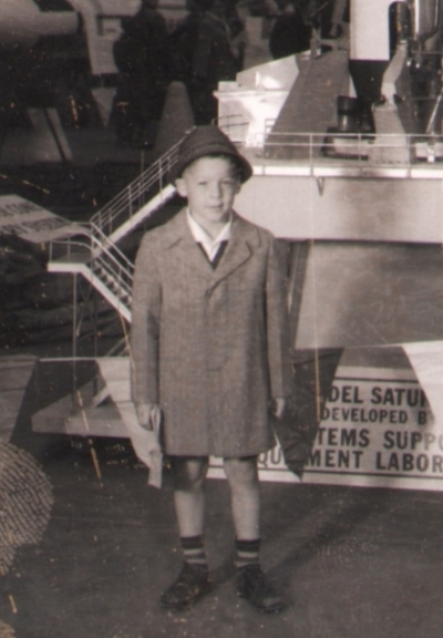 The artist at age five or six, in front of a model of a Saturn rocket launcher