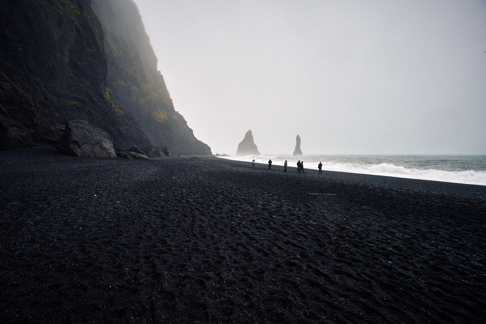 The basalt sea stacks far ahead are called Reynisdrangar. Local legend says there were two trolls pulling a three-mast ship to the shore unsuccessfully, and were caught by the sunlight at dawn turning them into stone