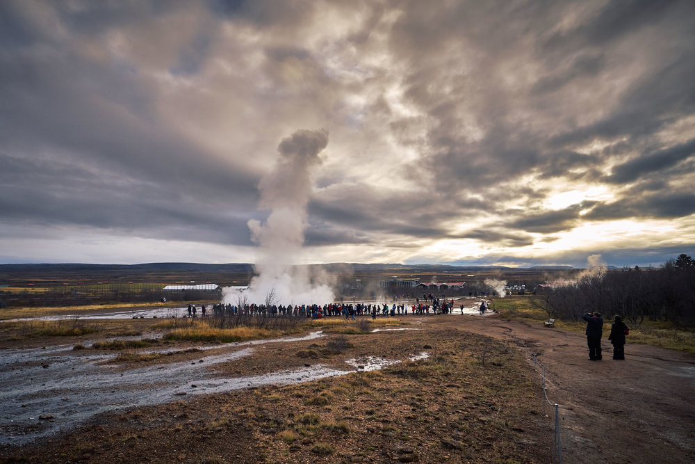 Strokkur geyser erupting from a distance, humans as scale. This is probably the most famous geyser in Iceland due to it's frequent eruption and height. Not as tall as the original Geysir but still pretty tall. It's a pretty impressive sight considering it's all resulting from natural force.