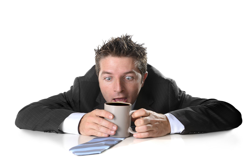 homme d'affaires tenant une tasse de café, visiblement halluciné  et stressé