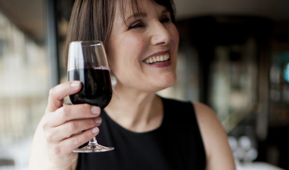 Karen levant un verre de vin rouge