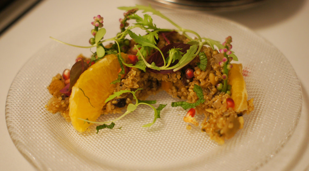 Quinoa and pomegranate salad, fresh orange slices, red onion and mint as the appetizer