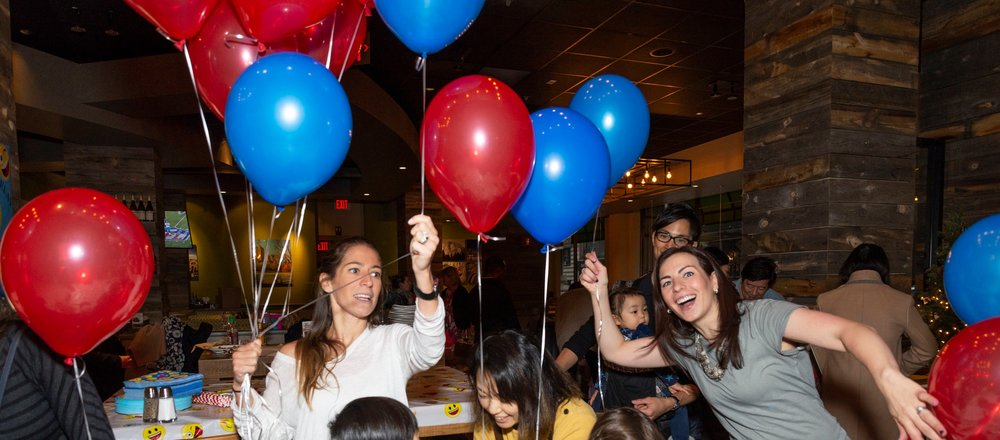Once we got all the chairs set up, we finally got to attach the balloons to the chairs. Here is my friend Laura helping pass out balloons for parents to tie to the chairs away after the party started.