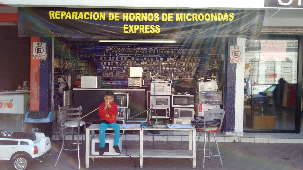 A boy watches a shop in Guadalajara, Mexico.