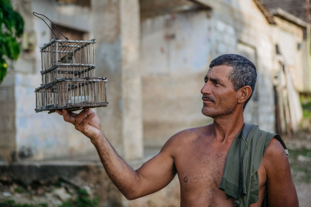 Man with caged bird in Gibara