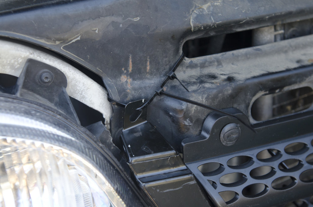 Zip tie through extra attachment point on the left side of the grille