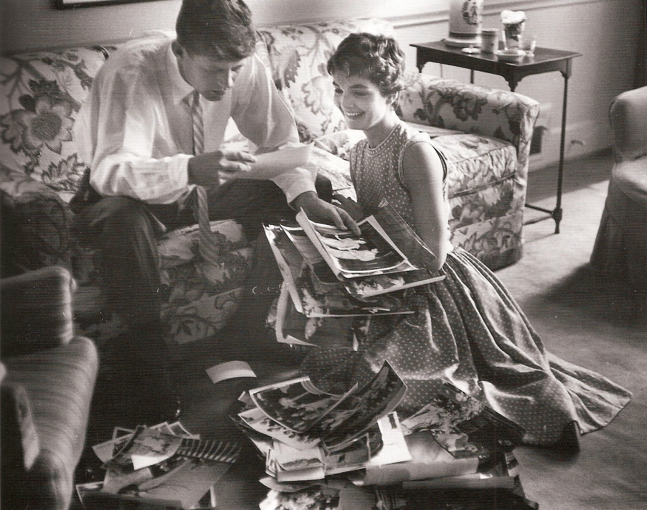 thekennedydynasty :      Jack and Jackie browsing through a newly unpacked box of wedding photos, May 1954   Photograph by Orlando Suero