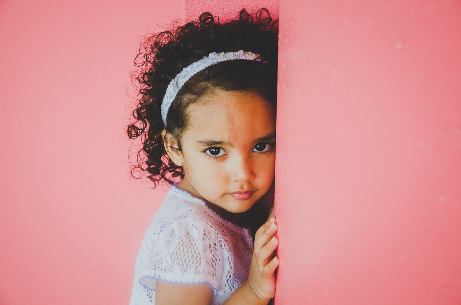 cute girl on a pink background is photographed in downtown indianapolis by photographer, Ashlee Lauren