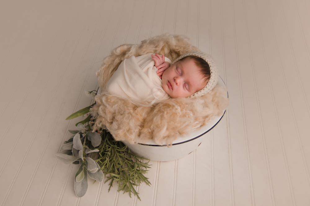 newborn girl is photographed in a prop bucket in Indianapolis
