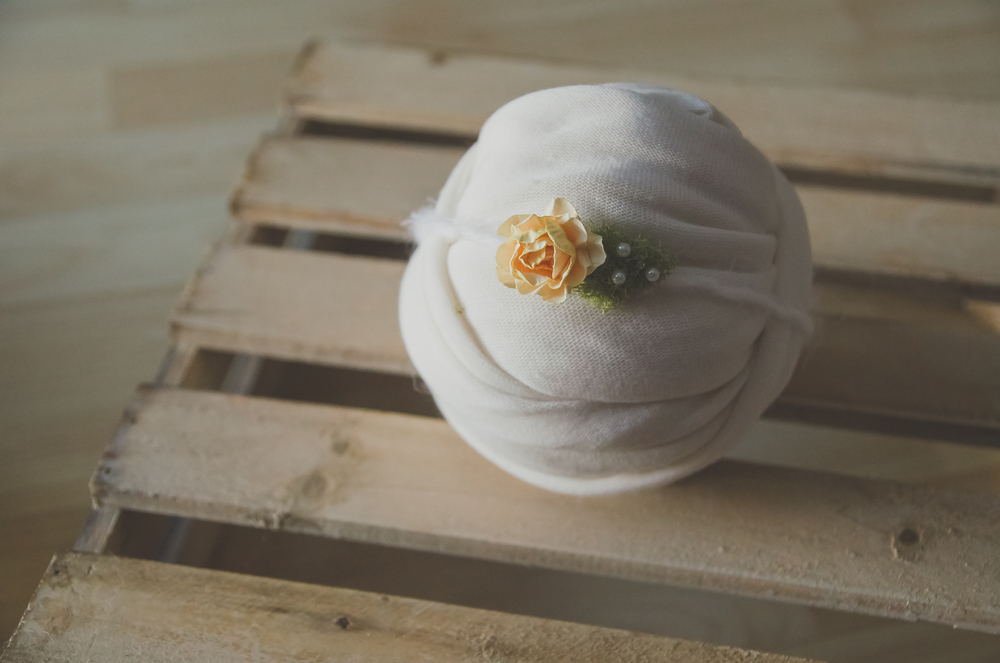 a pretty baby headband made out of a yellow rose and moss