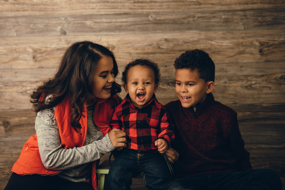 Brother and sister with baby brother pose for pictures