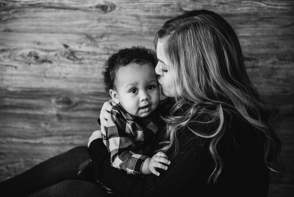 black and white photo of mom kissing baby boy