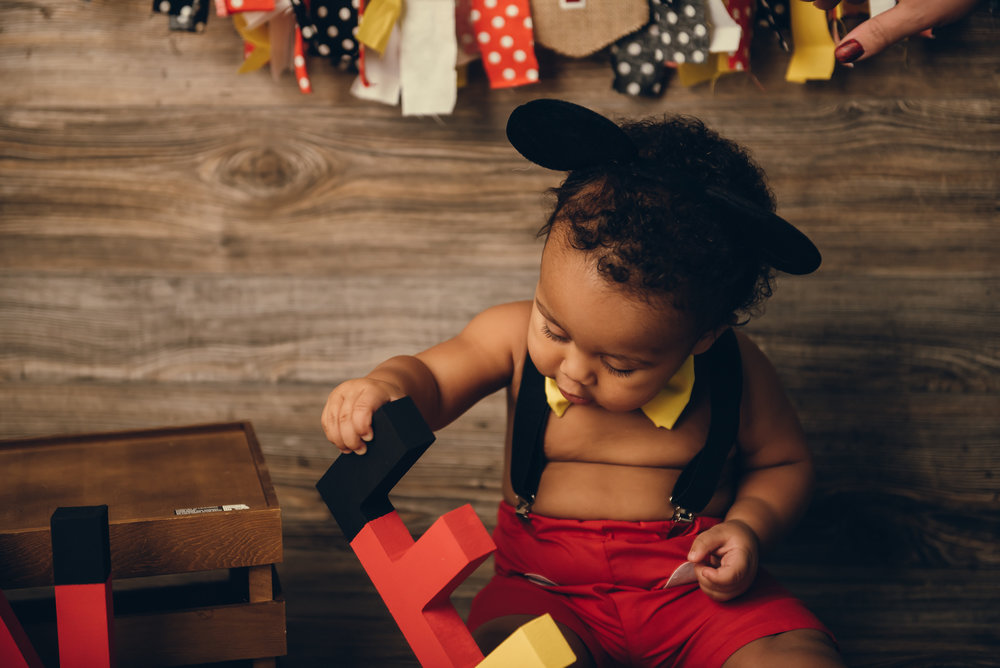 baby plays with first birthday decorations