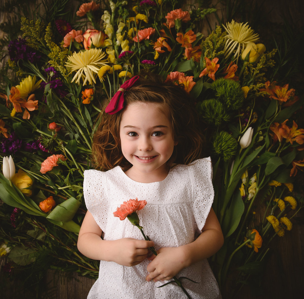 A little girl is surrounded by pretty spring flowers during her session with Indianapolis photographer Ashlee Lauren