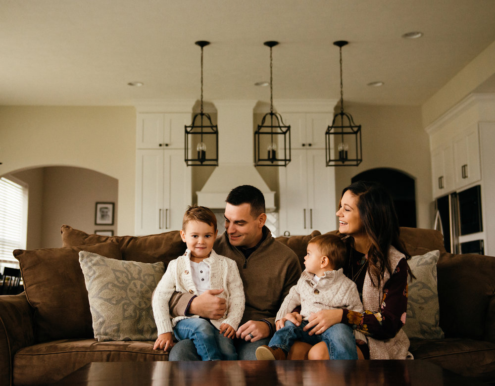 a family sits on the couch in their Fishers, Indiana custom home