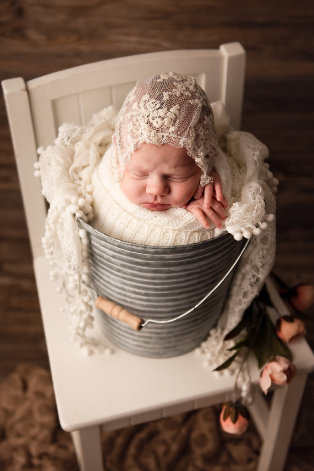 newborn is posed in a bucket for a photography session