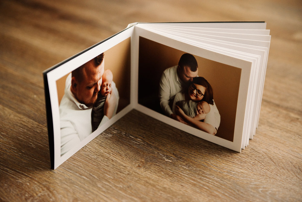 layflat album with photos of a family with their newborn baby