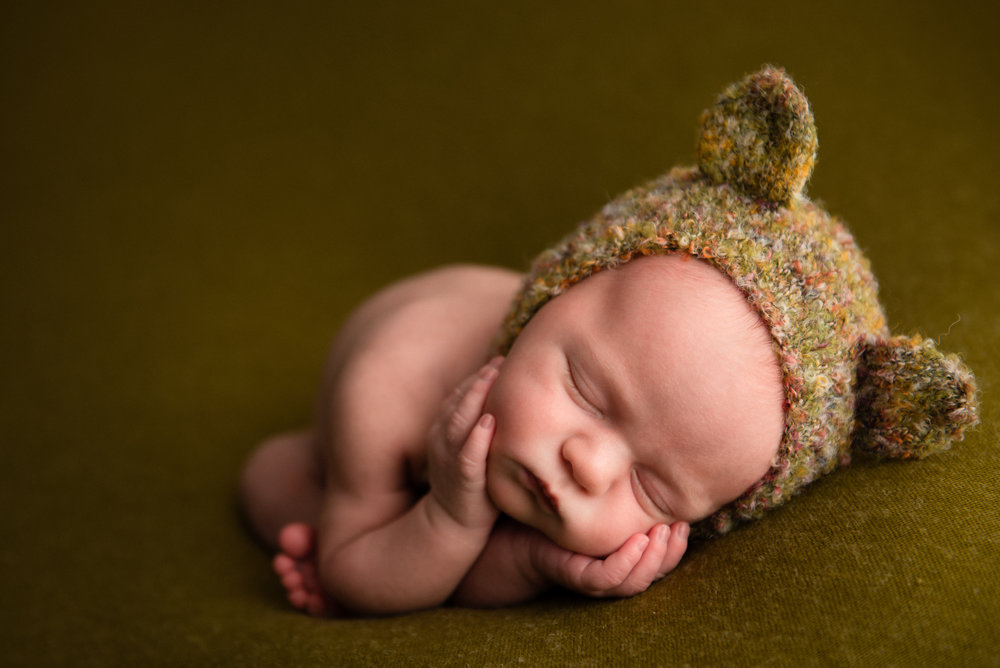parents pose with their newborn at an indianapolis newborn photography studio