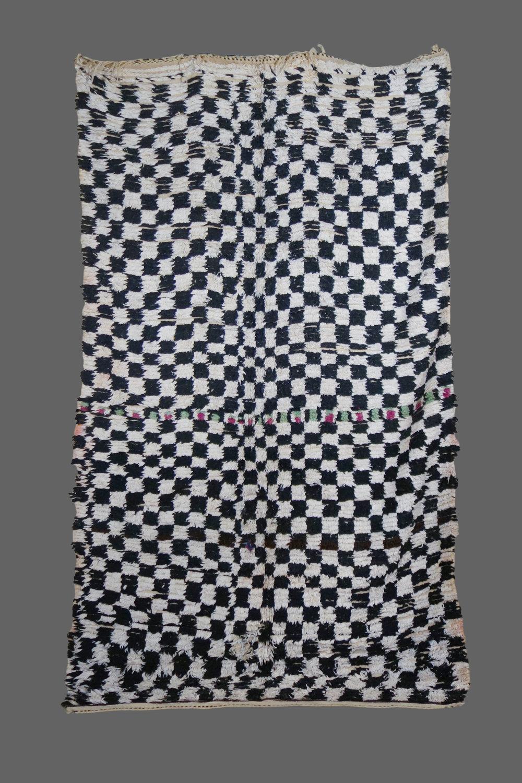 Ethnie : Azilal  Origine : Maroc, Haut Atlas  Année :1980  Dimensions : 3,00 x 2,00  Technique : Noeuds simples, fait main, laine épaisse  Description : Beau tapis damier noir et blanc. la ligne du centre en fait toute son originalité  Référence : AZL 015  Prix : 900€