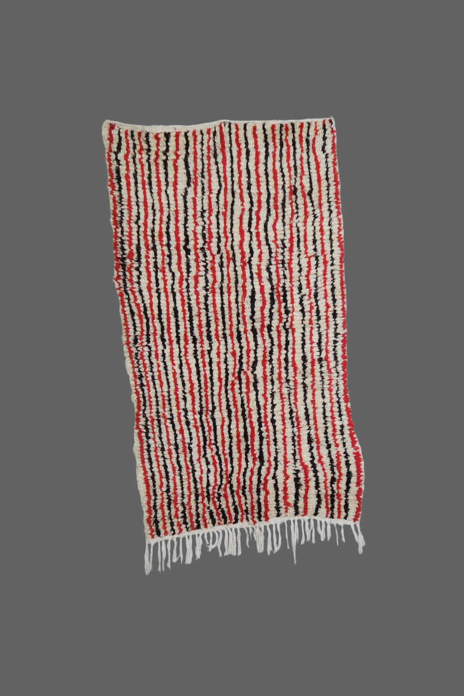 Ethnie : Azilal  Origine : Maroc  Année : 1980  Dimensions : 1,80 x 0,70  Technique : Noeuds simples  Description : petit azilal original, avec ces lignes de différentes couleurs  Référence : AZL 016  Prix : 650€