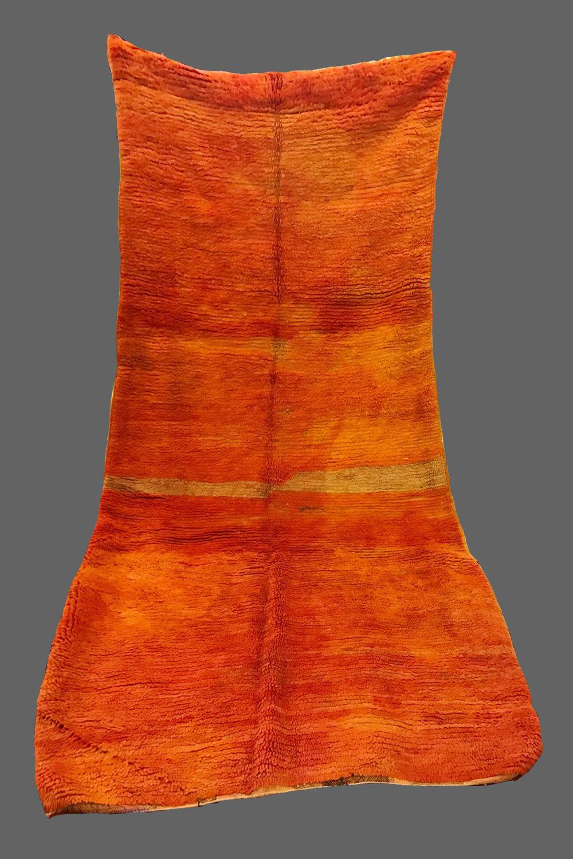 Ethnie : Beni m'guild    Origine : Maroc, Moyen Atlas    Année : 1980    Dimensions :    Technique : Double noeuds    Description : Tapis atypique, pas droit, presque en forme de cape. très beau dégradés d'orange    Référence : BMG 005    Prix : 800€