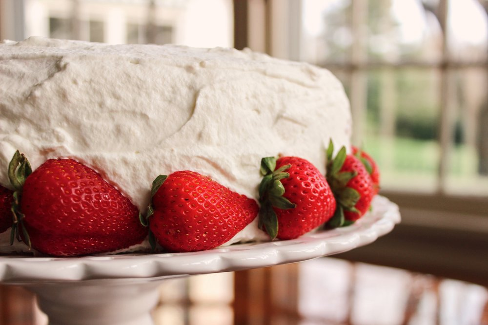 Completely cover assembled cake in whipped cream and garnish with berries.