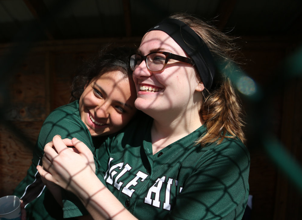 Andrea Calvert and Helene Yadgood embrace in the dugout before a game against Paulo Friere on May 2, 2017 at Eagle Hill School's Pioneer Field in Hardwick, Mass.