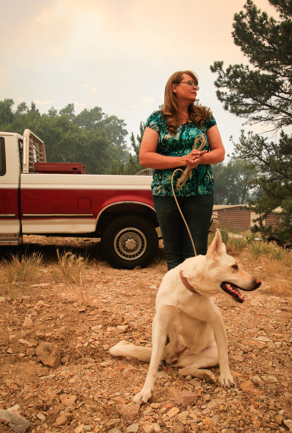 "Homeowner Angie Loyning, standing with her dog Lady, discusses her family's long history in Landusky, as the July Fire spreads behind her house. ""My family's been here for almost 100 years,"" she said."