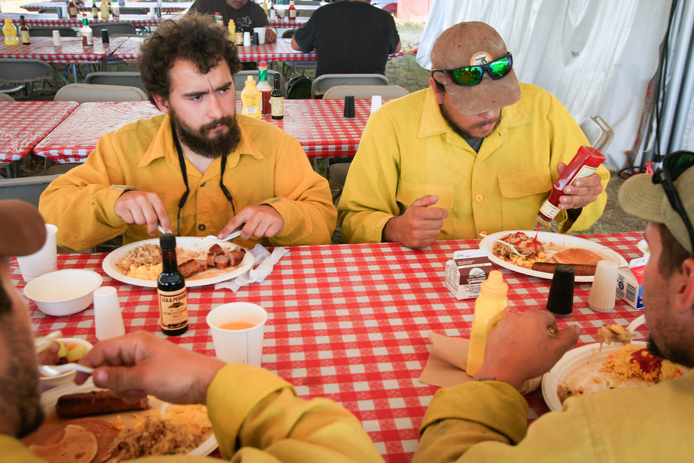 Firefighters Stephen Slonosky and Christopher Pickering eat breakfast after a 16-hour overnight shift and before getting some rest at the fire camp in Zortman, Mont. on July 7, 2017.