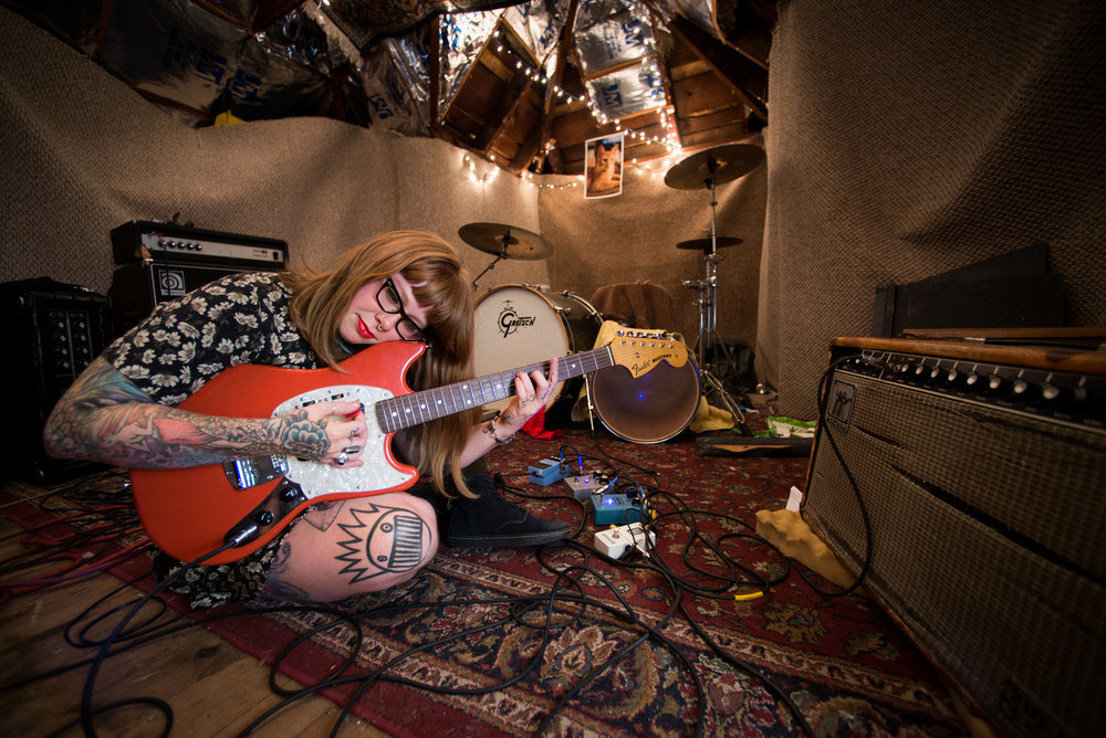 "Jesse Amesmith and her guitar ""Big Red"" in her sound studio and band practice room, in the attic of her apartment in Rochester, NY."