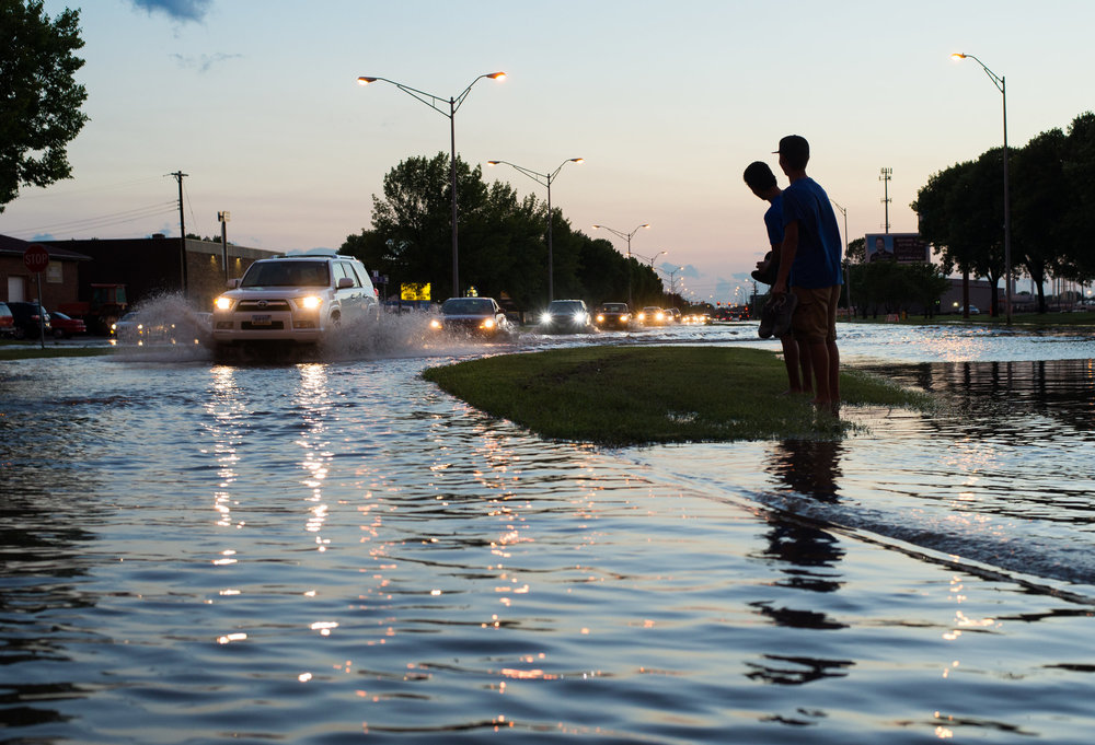 Aaron Yeban and Taiylor Schafer look out over Demers Ave from the median as they wait for their friend to get out of traffic, which was stopped due to flash flooding in Grand Forks, N.D. on July 19, 2016.