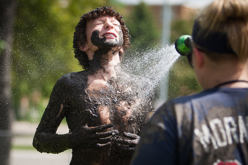 Theo Sum gets sprayed down after participating in International Mud Day at the University of North Dakota Children's Learning Center on June 29, 2016 in Grand Forks, N.D.