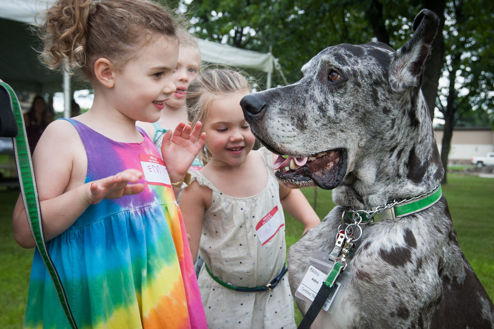 Emily Petricig and her cousins, Evangeline and Ruby Johnson-Richards, pet Astro the therapy dog at the Cherished Children Memorial Service held outside of Altru Hospital in Grand Forks, N.D. on August 9, 2016.