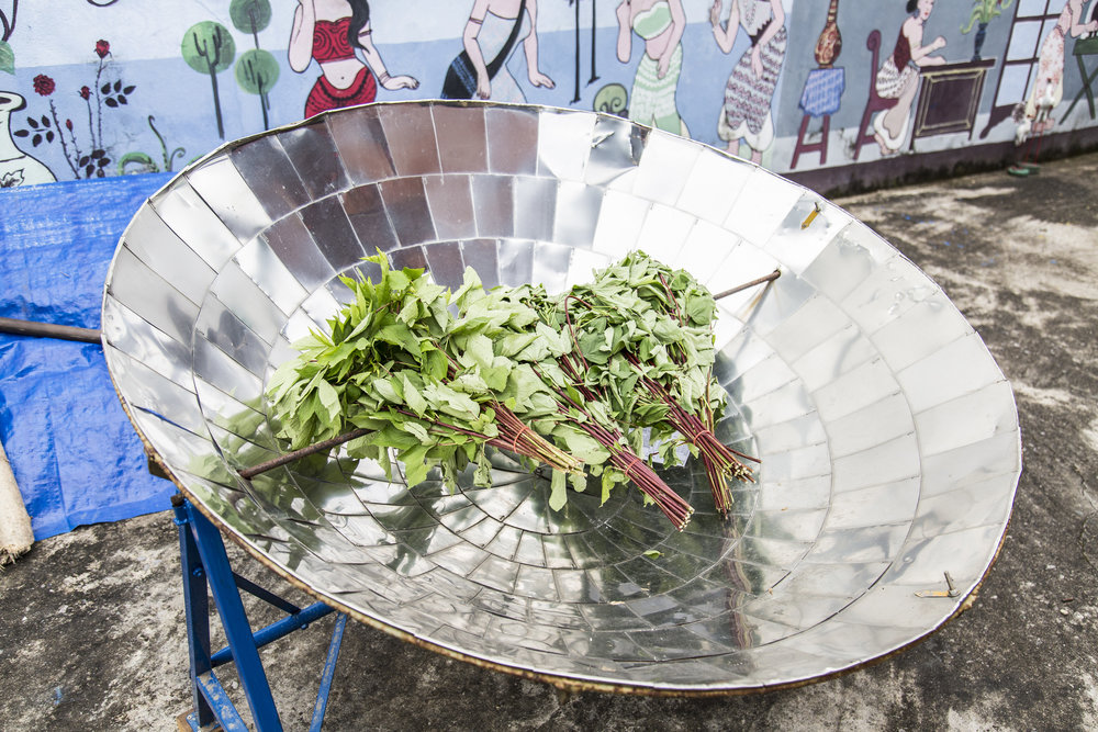 Vegetables dry outside on a big metal satellite dish looking bowl.