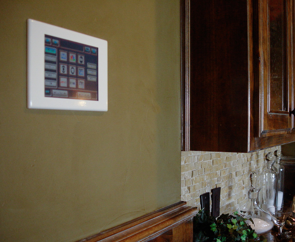 The Elan in-wall touchscreen controls audio and video, lighting, shades, and air conditioning