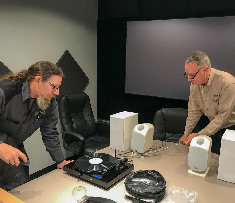 Pat Murray and Pat Johnson set up a new Project turntable for a client. It's a Christmas present for our client's daughter. This evening he'll select a pair of speakers: either B&Ws or Tannoys. Ixos cabling.