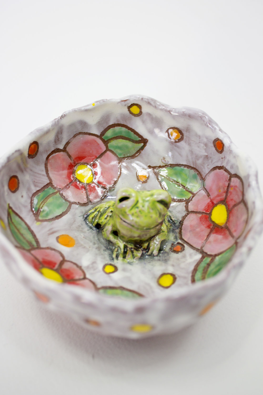 Hand-pinched bowl, with carved frog and drawn floral motifs